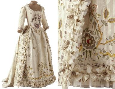 Vers 1780-85  Pékin brodé. Soie Inv.29796 Cette robe est une robe parée, portée pour les bals.  La ligne de la jupe, sur un panier beaucoup moins ample que le panier de la robe à la française, caractérise le début des années 1780.   Les parements sont décorées de fleurs peintes en tissu, de volants de gaze,   et de broderies polychromes d'une délicatesse extrême qui est typique des toilettes   créées par Rose Bertin, célèbre marchande de modes fournissant la reine Marie-Antoinette.