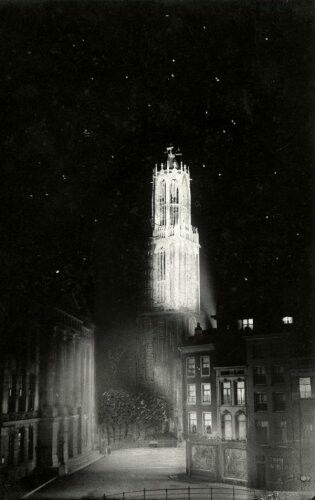 De verlichte Utrechtse Domtoren bij avond. Utrecht, Nederland, 1918.