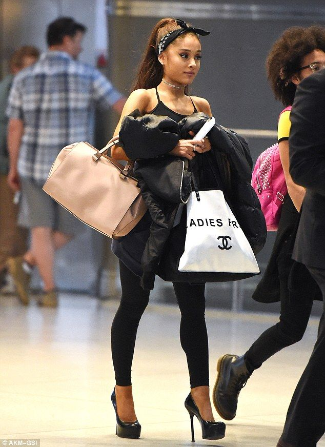 No diva here! Ariana Grande, 22, lugs her own bags through JFK airport on Monday...