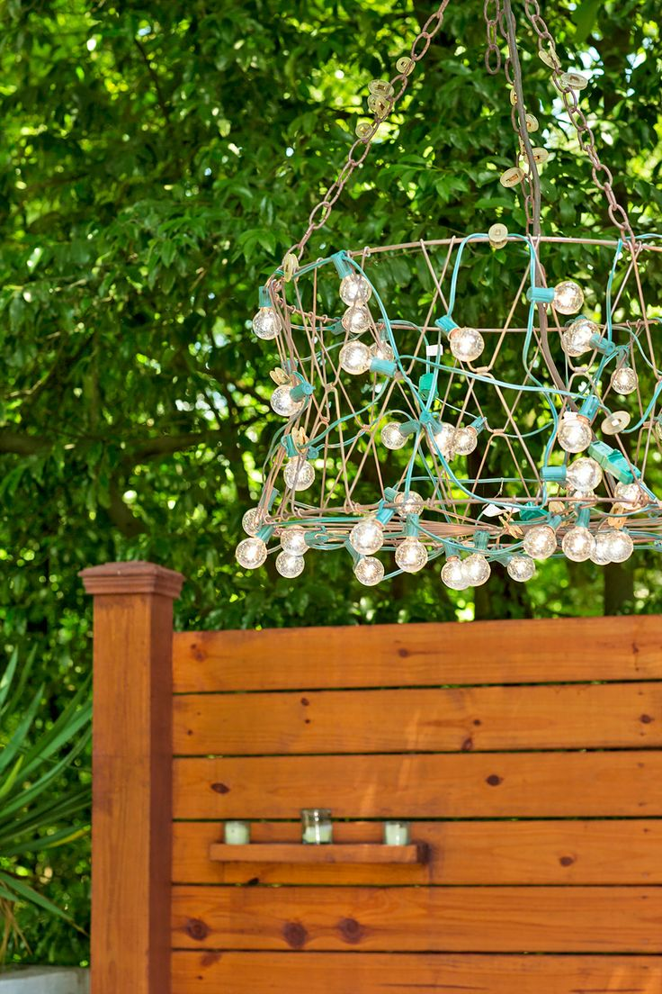 Buck fashioned a custom outdoor chandelier using commercial string lights, a wire basket, plastic clips, and chain.