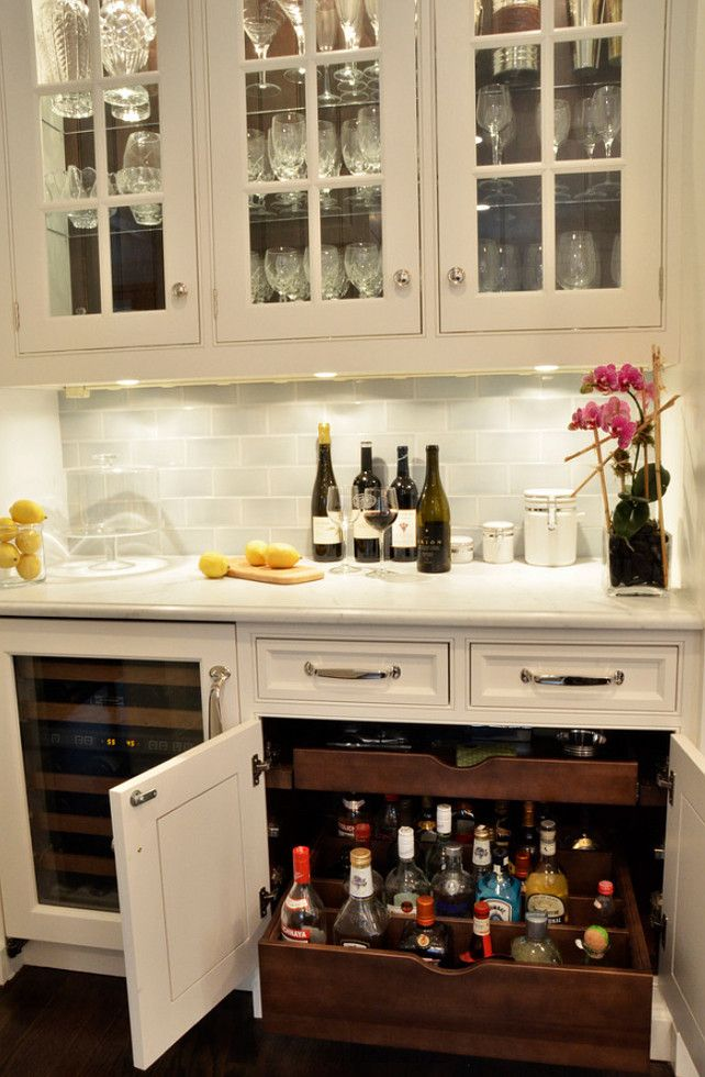 Bar Cabinet Design: Custom pullouts were designed to hold liquor bottles upright, with adjustable dividers to keep them from tipping.