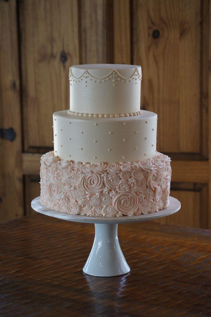 Elfenbein und hellrosa Buttercreme-Hochzeitstorte. Zufällige Rosetten auf der Unterseite …   – hochzeitstorte