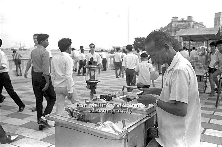 """National Day Parade 1966 at the Padang - Hawker selling """"Kueh tutu"""", a local snack, along Queen Elizabeth Walk at the Esplanade where a crowd has gathered for the fireworks display"""