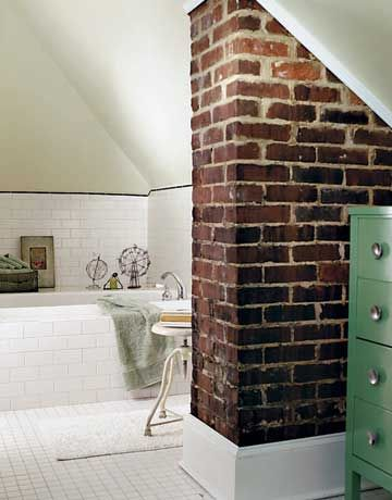 bath in the attic. exposed brick chimney column.