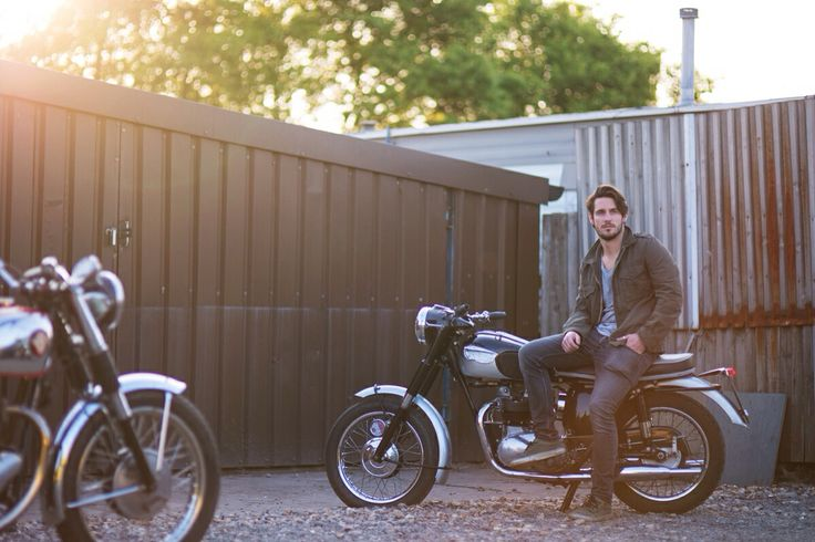 Male model sitting on a Triumph motorcycle outside shuttered workshops. Backlit by low evening sun. #triumph #motorcycles #deuscustoms #sevenwolves
