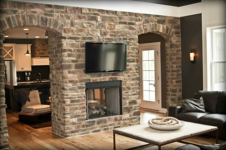 Absolutely amazing double stone archway with a see through fireplace between the living room and kitchen.