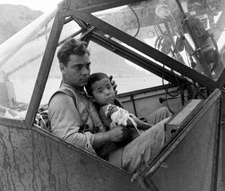 An American soldier cradles a wounded Japanese boy and shelters him from the rain in the cockpit of an airplane during the Battle of Saipan while waiting to transport the youngster to a field hospital. July, 1944. [OS][1500 × 1269] : HistoryPorn