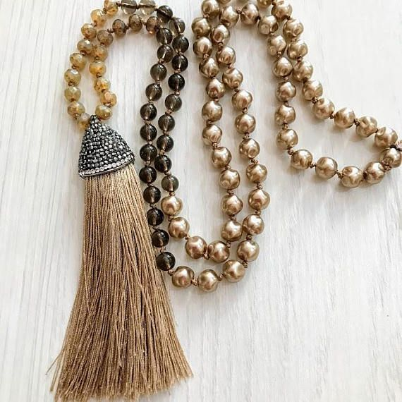 This stunning Bohemian necklace is hand crafted with gorgeous 6 mm faceted natural antique gold color beads , 8 mm mocha pearl and 6 mm smoky beads . The Tassel pendant is natural antique gold color It is the perfect stylish neutral necklace for everyday wear I have used these great