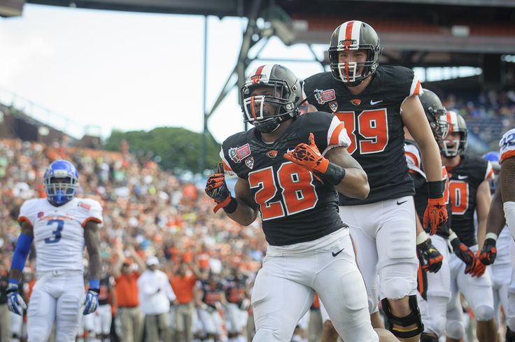 Terron Ward scoring a touchdown against Boise State in 2013 while wearing a black uniform top and white pants. #gobeavs #oregonstate #beavers #uniform