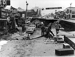 The 1964 Alaska earthquake, magnitude 9.2,  began at 5:36 P.M. AST on Good Friday, March 27, 1964. Across south-central Alaska, ground fissures, collapsing buildings, and tsunamis resulting from the earthquake caused about 143 deaths (9 from quake, others from tsunamis).  Lasting nearly four minutes, it was the most powerful recorded earthquake in U.S. and North American history. Fourth Avenue in Anchorage, Alaska, looking east from near Barrow Street.