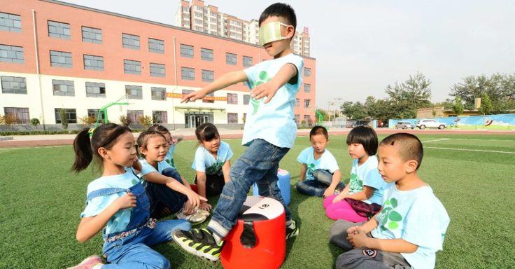 Crianças participam de atividade com os olhos vendados em uma escola primária de Xingtai, província de Hebei, norte da China. A ideia é que os alunos experimentem um pouco da vida dos deficientes visuais durante a atividade extracurricular.  Fotografia: Xinhua / Zhu Xudong.