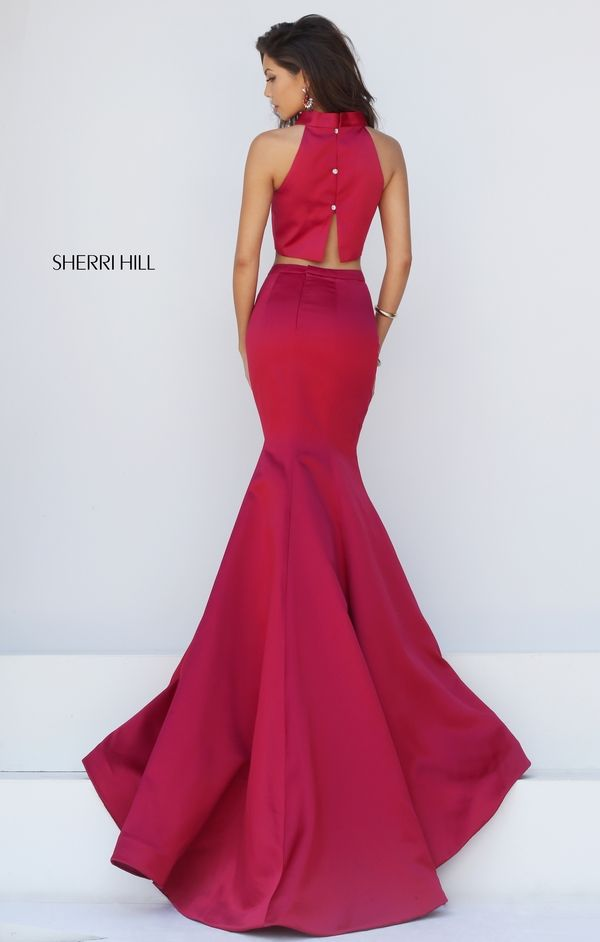 Exude understated elegance in the chic Sherri Hill 32365 two-piece prom dress with trumpet silhouette. This full-length sleek ensemble needs no embellishments. The slight crop top showcases a jewel collar neckline framed with cut-in shoulders. The back features three buttons below the collar and finishes in an open slit above the midriff. The trumpet skirt flares smoothly and features a pleated inset sweep train.