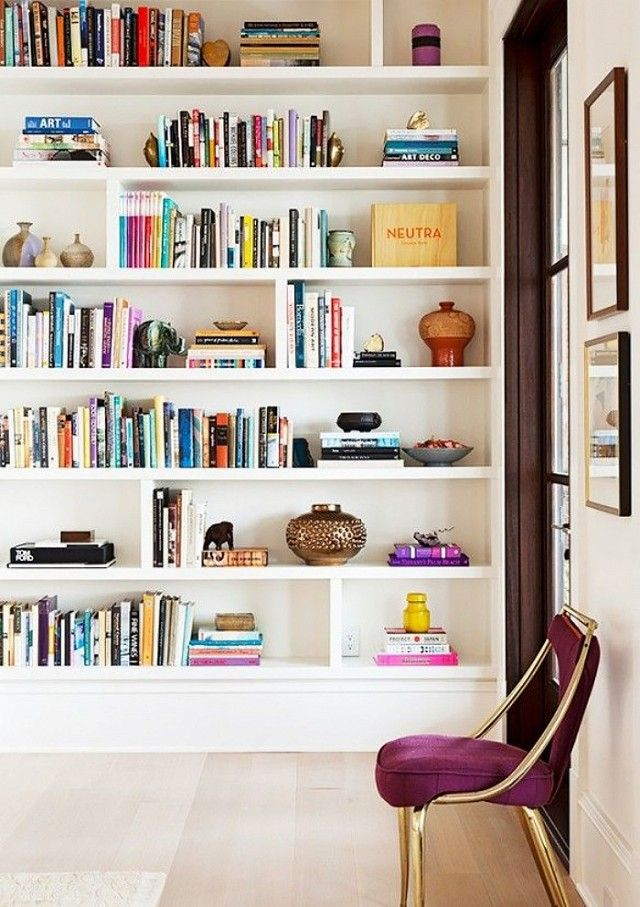 Floor-to-ceiling white book shelf filled with books, and a plum statement chair
