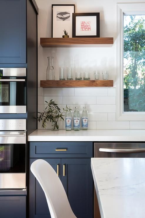 kitchen features navy blue cabinets adorned aged brass pulls paired with white quartz countertops that resemble marble and a white stacked tile backsplash.