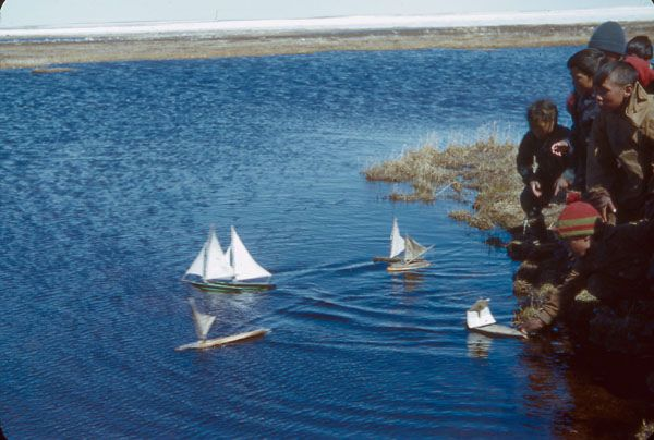Group of Inuit children sailing toy sailboats at water's edge / Groupe d'enfants inuits faisant naviguer leurs bateaux jouets au bord de l'eau   by BiblioArchives / LibraryArchives