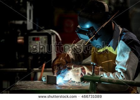 Industrial welding worker at the factory, welding steel with safety protective mask