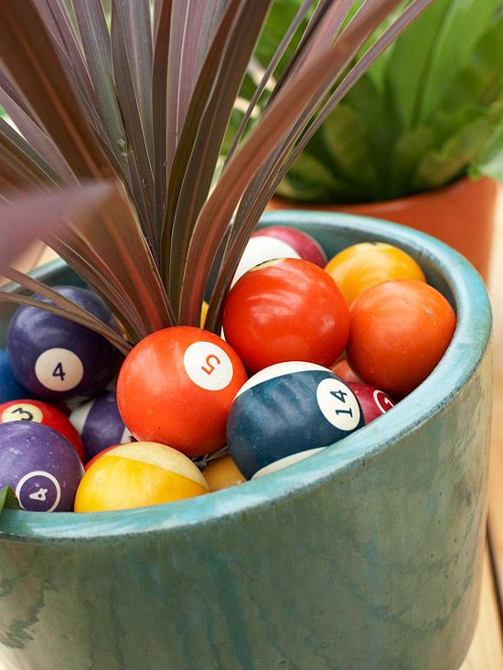 Pool balls were used to add a punch of color to green potted plants. Find other unusual items at flea markets, yard sales, and secondhand stores to bring character to your own outdoor spaces. As these planters prove, your accents don't have to be huge to make a fun impact. (But you may want them to be weatherproof!)/