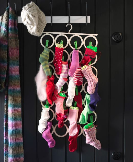 Ein KOMPLEMENT Aufhänger in Weiß hängt an Haken an einer schwarzen Holzwand. Im Aufhänger stecken verschiedenfarbige Socken, die mit kleinen Päckchen gefüllt sind.