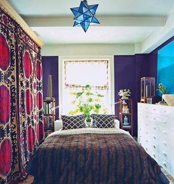 Domino magazine . Small bedroom.  Suzani curtains used instead of closet doors, rental apartment in NYC, purple painted bedroom walls.