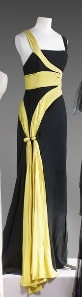 Jean Patou, haute couture, circa 1935-1938. Long dress in black crepe, yellow, the latter effect to surround the body ending at the hips by holding the two nodes segments; square neckline and wide straps on backless flowing skirt.