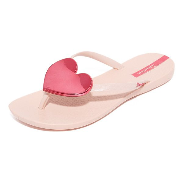 A sculpted, mirrored heart accents the slim thong strap on these rubber Ipanema flip-flops. Textured footbed and rubber sole. Fabric: Rubber.
