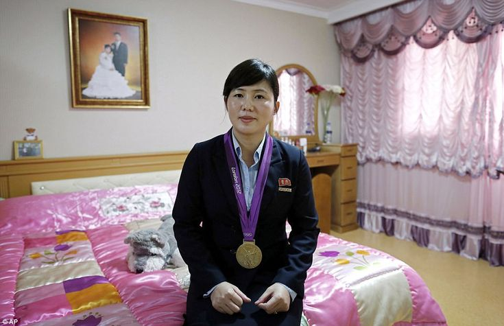 North Korean London 2012 Olympics Judo gold medalist, An Kum Ae poses in her bedroom with her gold medal in Pyongyang