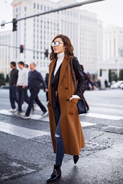 Genius. Leather jacket over a white turtleneck. Top layer, chestnut brown long, double breasted vest/coat, skinny jeans, ankle boots, black shoulder bag, mirror lens sunglasses