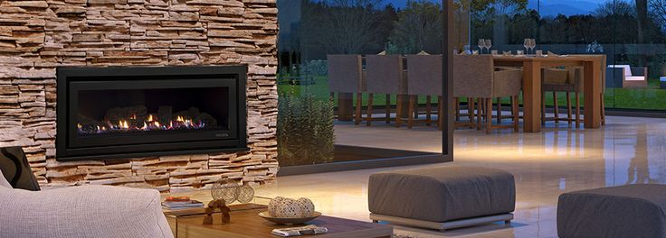 Escea DL1100 gas fireplace in a stone wall in an open style living space full of glass sliding doors