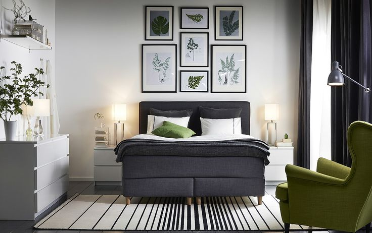 A bedroom furnished with a dark grey divan bed combined with white chest of…