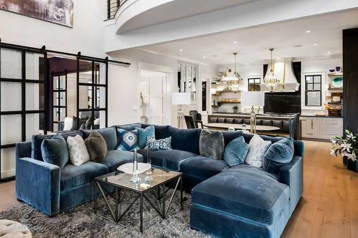 Two story contemporary living room showcases an eye catching blue velvet sectional with a chaise lounge accented with blue and gray velvet pillows and blue ikat pillows.