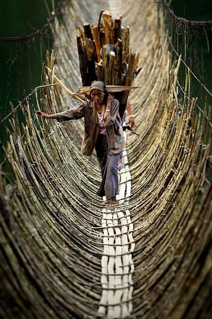 Porters crossing a hunging bridge, Himalaya.