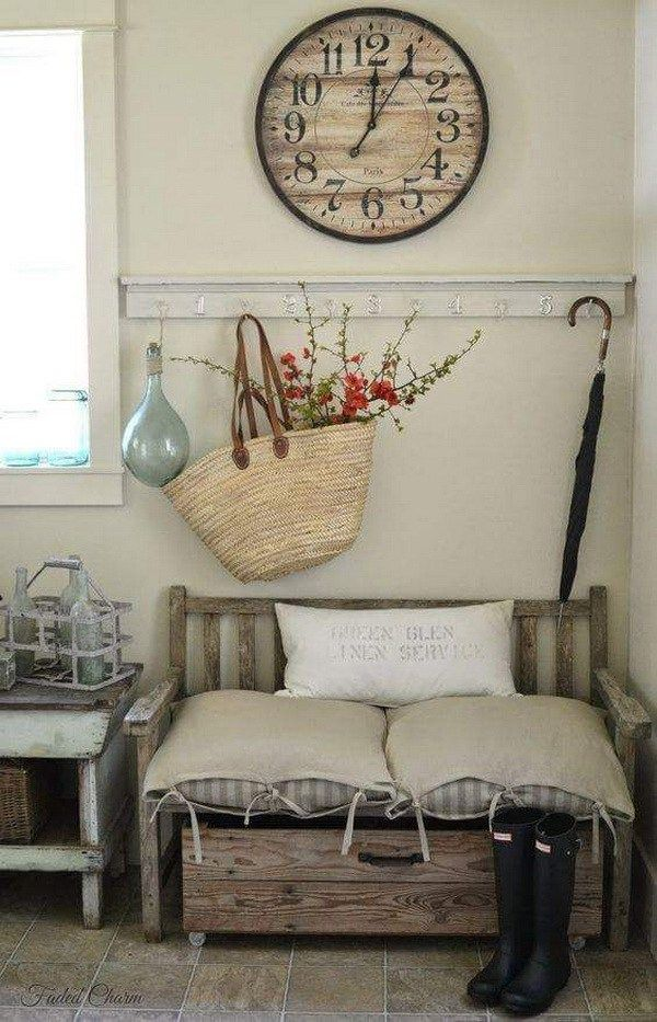 Shabby chic decor with a sisal woven basket with flowering branches. The gray walls and the rustic wooden bench add more earth charm to this space.