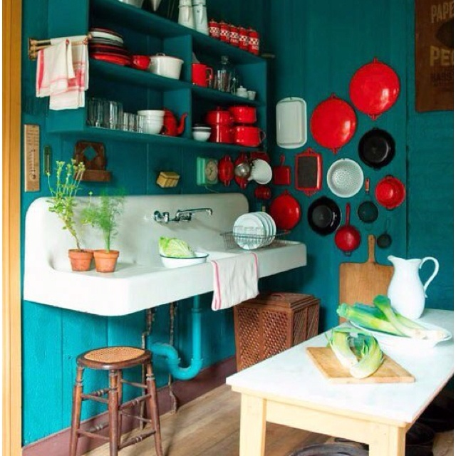 Absolutely love the deep turquoise painted wood panel walls with the bright red accents.