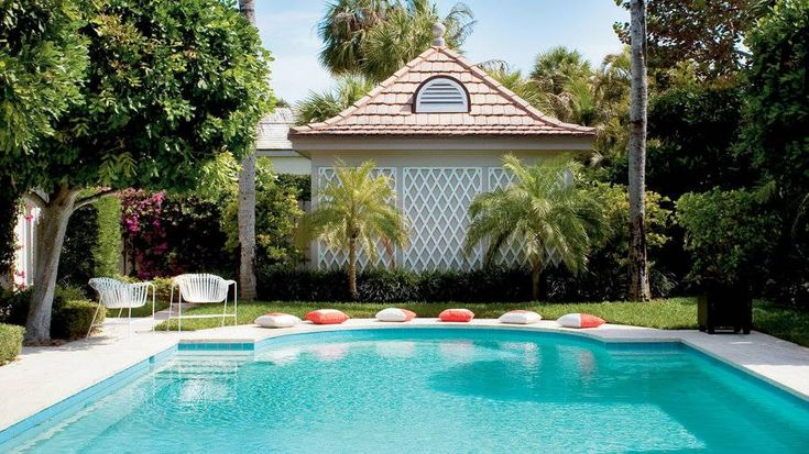 Why We Love It: The deep orange throw pillows complement the bright aqua of this Florida pool. Vintage chairs that feature curvy shapes echo the pool's outline and give the space a chic vibe.