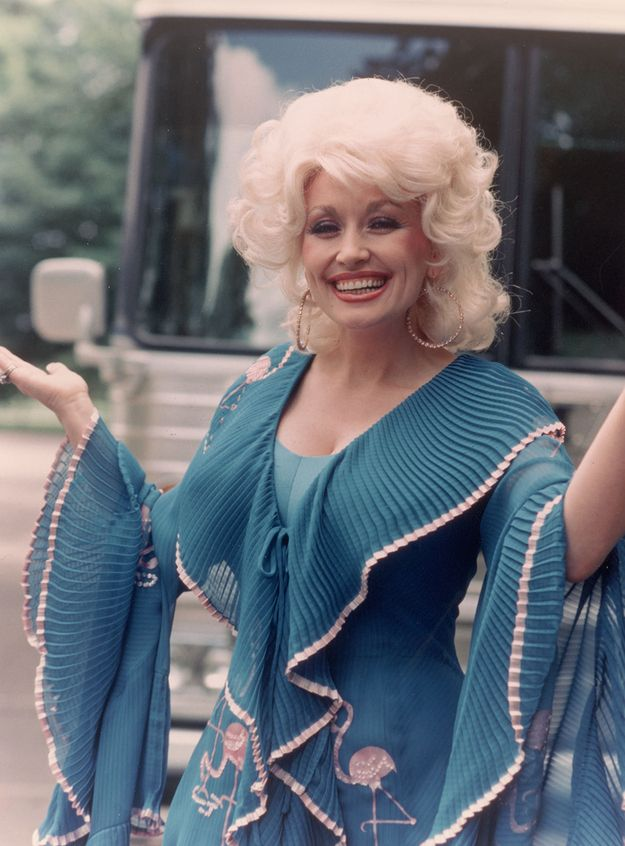 And these accordion pleated blue beauties on a flamingo-print dress. | 19 Of Dolly Parton's Most Fanciful Sleeves