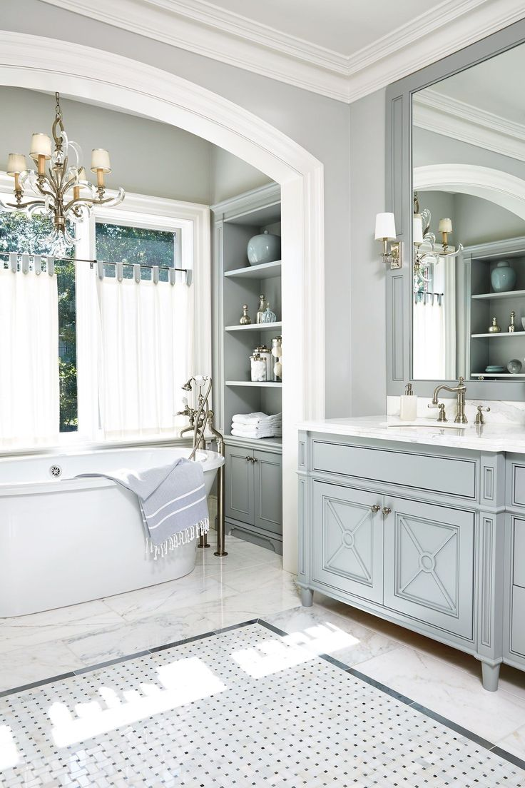 A beautiful arched nook houses the tub in this all-gray bath.