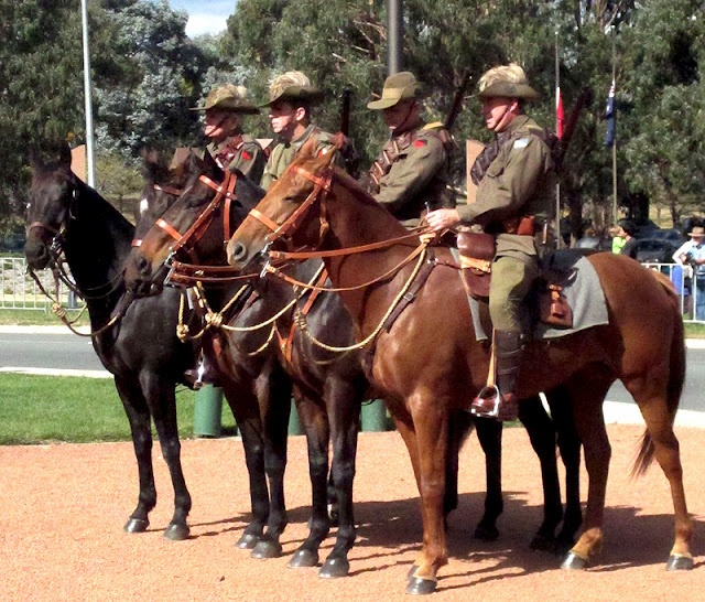 This photograph was taken by someone who attended the 2011 ANZAC Day ceremony at the Australian War Memorial. The mounted soldiers are wearing what is believed to be the uniform of the WWI Light Horsemen, with slouch hats featuring the rising sun badge. Many Anzac Day ceremonies now feature volunteers representing the famous mounted cavalry units. They took part in the last great successful cavalry charge to take the wells at Beersheba in WWI.