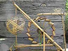 a bamboo waterwheel powers a vertical axis bamboo ball flywheel