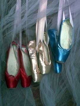Different colored toe shoes that would appear to be hanging from inside a tu tu