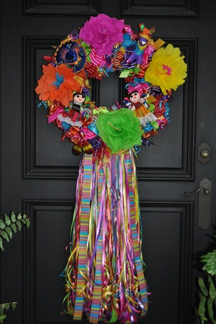 """Our top seller! This is our fabulous """"Fiesta San Antonio"""" Wreath in the traditional size - Medium. It is approximately 22"""" in size and is filled with festive ribbons, mexican paper flowers, sombreros, pinatas, indian dolls and sarapes. This one is sure to bring a delight of mexican culture to your front door!"""
