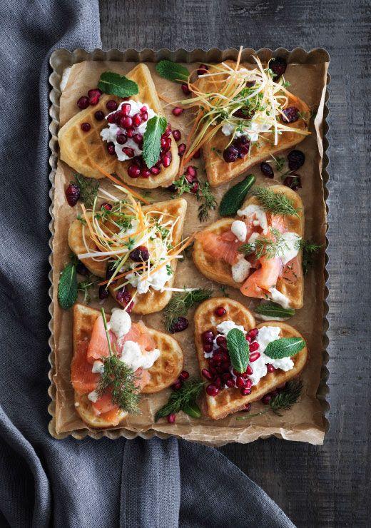 Uma forma e papel vegetal com waffles em forma de coração espalhados, com toppings diferentes como mirtilos vermelhos, queijo fresco, legumes e salmão marinado