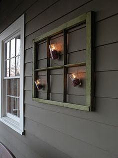 outdoor holiday decor...mason jars, cranberries & tea lights hanging from old window