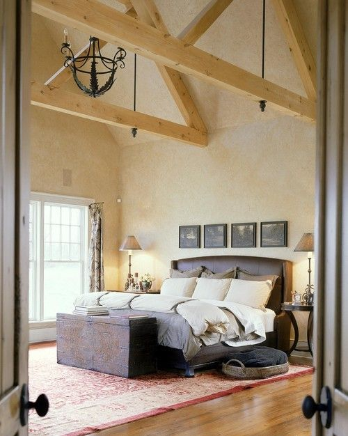 Eine schmiedeeiserne Leuchter und leicht getönten Holz Sparren betonen hohen Gewölbedecke dieses Master-Schlafzimmer. Foto von Witt Bau