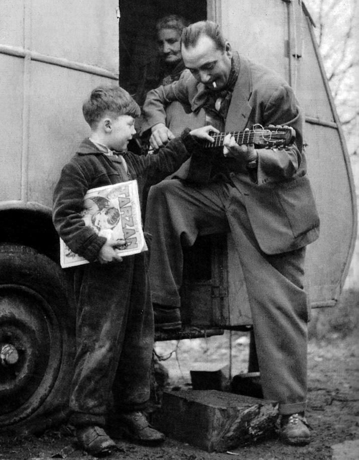 Django allowing a young friend to touch his guitar.