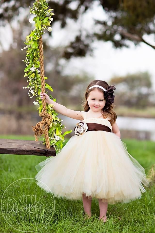 This dress is a classic! A gorgeous blend of ivory and champagne tulle, accented with a chocolate brown sash and handmade flower. The flower features tons of layers in all three shades, ivory, champagne and brown, and has a vintage inspired rhinestone center. A perfect dress for your flower girl in any season! And remember, []