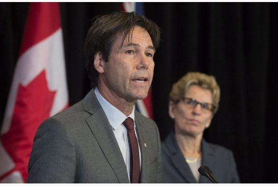 In this file photo, Ontario Health Minister Eric Hoskins speaks as Premier Kathleen Wynne looks on in Toronto on Monday October 20, 2014.
