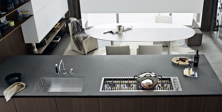 A detail of the worktop in quartzite raven sand, under top-mounted sinks in steel and personalised hob Varenna by Scholtes in stainless steel with four aligned burners.