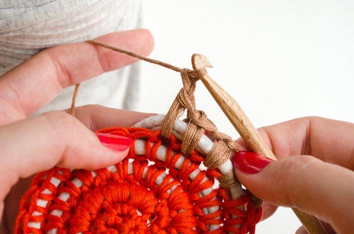 Crocheting fabric with yarn to make a rug