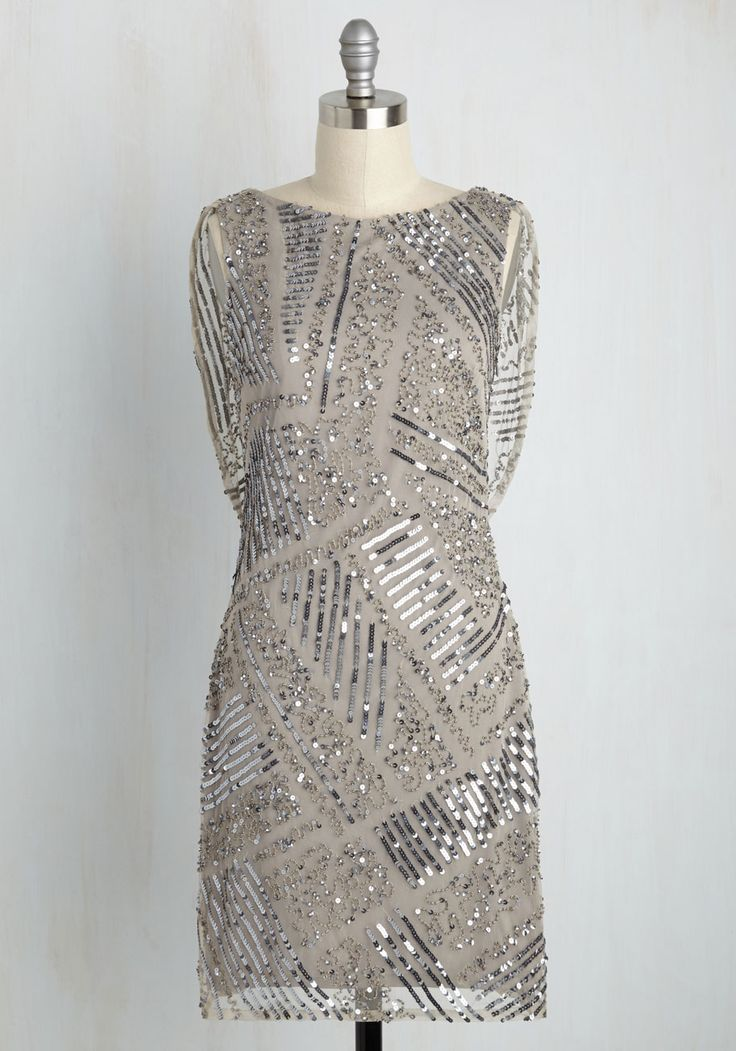 For all you do, let this grey shift dress be your much-earned indulgence! Gussy up with the geometrically placed sequins and beads atop this deco-meets-modern frock, relish in its elegantly draped back, and revel in the majesty that comes from being a wonderful person with even greater style!