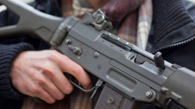 Sur le balcon avec un fusil d'assaut